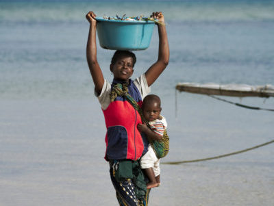 African woman with baby carrying a bucket filled with crab on her head. Coast of Benguerra Island. Mozambique. (c) Martin Harvey / WWF